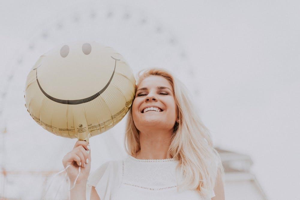 Mulher segurando um balão e sorrindo