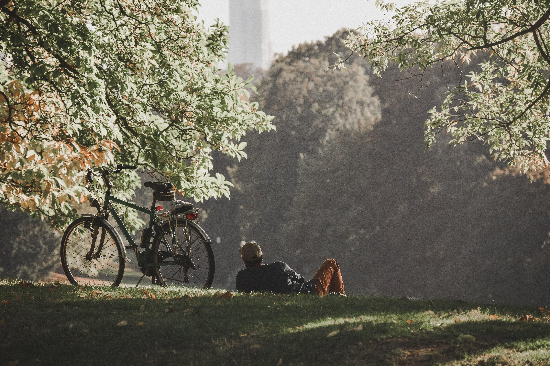 Homem deitado, ao lado de sua bicicleta, no gramado de um parque muito arborizado.